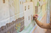 An artist works on a mural at a church.