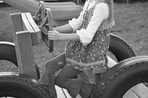 A child driving a toy car on a playground
