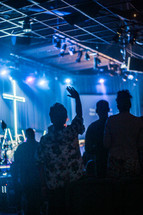 hands raised and musicians singing during a worship service