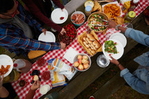 overhead outdoor picnic with food on a table and gingham tablecloth