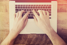 hands typing on a laptop computer on a desk