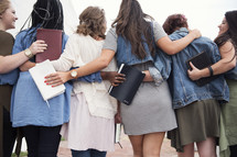 women walking together carrying Bibles.