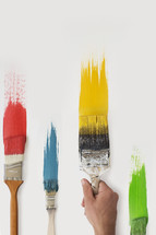 Paint brushes and colorful paint on a white canvas.