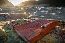 journal on a blanket in the sand