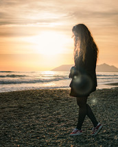 a woman in a coat standing on a rocky beach at sunset