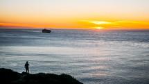 a man standing on a beach shore at sunset