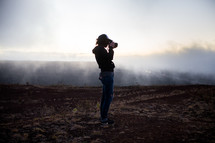 woman holding a camera in a foggy field
