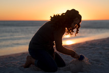 a woman building a sandcastle in the sand at sunset
