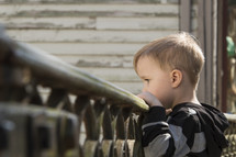 a toddler boy looking over a railing