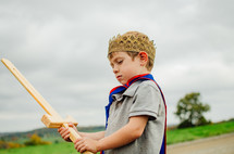 A young boy wearing a cape and crown  holds a wooden sword.