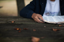 torso of a young man reading a Bible outdoors