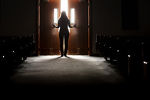 Silhouette of a woman leaving the church sanctuary.