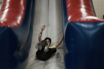 a boy sliding down a bouncy house slide at a carnival