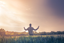 Man standing in the field with hands raised in prayer and worship.