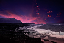 ice along a shore and pink clouds in an indigo sky