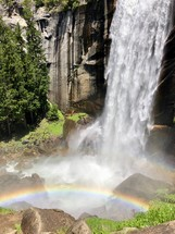 rainbow at the bottom of a waterfall