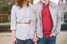 couple holding hands, standing outside