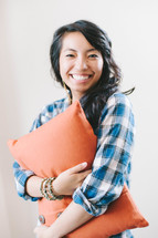 Woman hugging an orange pillow