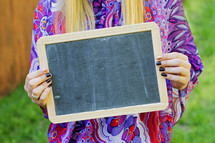 a woman holding a blank chalkboard sign