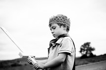 A young boy holds a sword outside wearing a cape and crown.