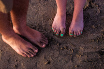 couples bare feet in the sand