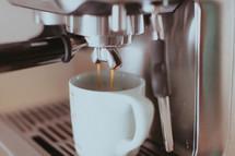 A double espresso shot pouring into a coffee mug.