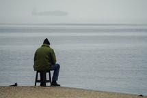man on a stool along a shore