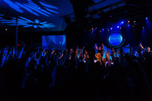 worship service, crowd lifting hands, worship leader,