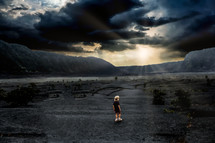 a man standing under cloudy skies in a valley