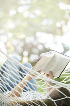 woman reading a Bible in a hammock