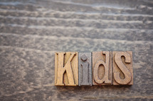 wooden print press stamps forming the word kids