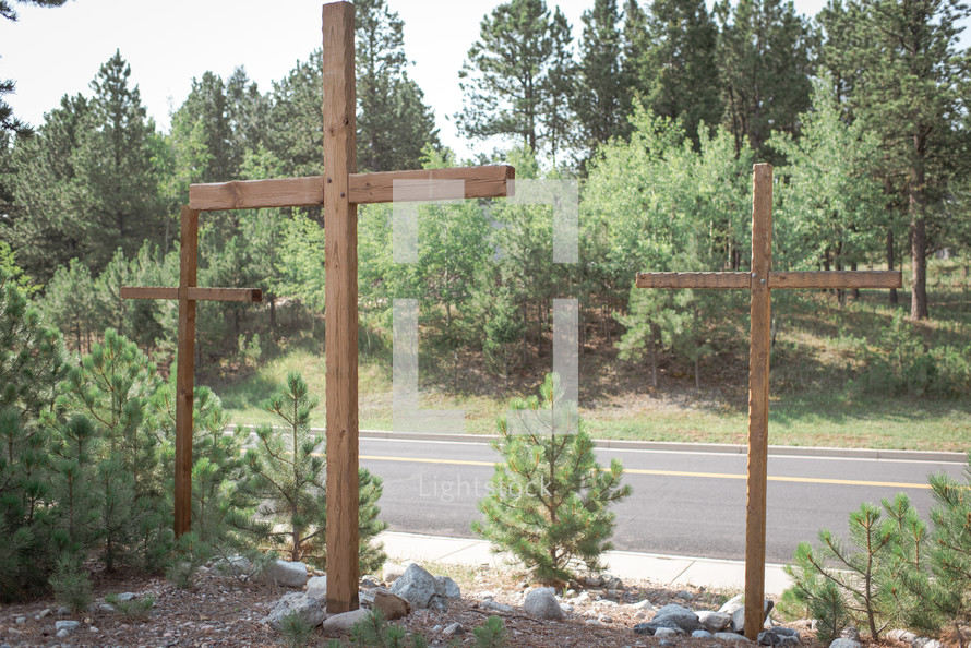 three wooden crosses by the side of a road