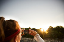 a woman taking a picture of the sunset with her cellphone