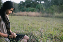 A young woman sitting and praying in a field of grass.