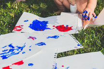 a toddler finger painting in the grass