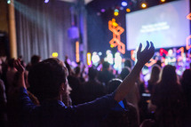 raised hands of parishioners at a worship service