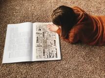 a child reading a Biblical comic strip