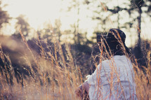 a woman sitting in a field of tall grasses