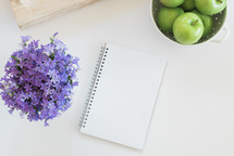 purple flowers, journal, notebook, cauldron, apples, green apples, wood bowl in kitchen