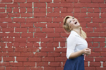joyful teenage girl laughing in front of a red brick wall.