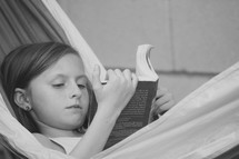 a little girl reading a book in a hammock