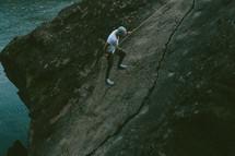 man scaling a rock face
