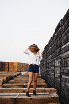 woman posing in front of stacked pallets