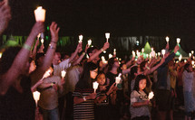 a crowd holding up candles at a worship service