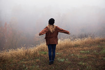 a woman standing on a foggy hill with outstretched arms