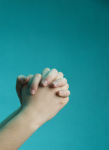 praying hands against a blue background