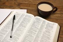 pen on an open Bible and coffee mug