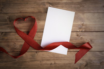 red ribbon in the shape of a heart and blank paper