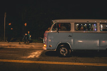 a VW van driving on a road at night