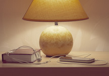 lamp, Bible, cellphone and earbuds on a nightstand